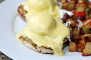 Eggs Benedict and Diced fried potato. Breakfast or Brunch
