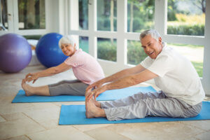 Senior couple performing stretching exercise on exercise mat at